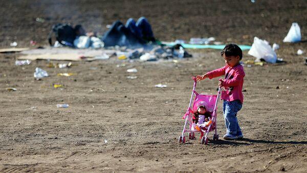 Девочка с коляской в лагере для беженцев на сербско-венгерской границе