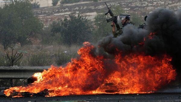 Силы безопасности Израиля рядом с горящим участком дороги. Архивное фото