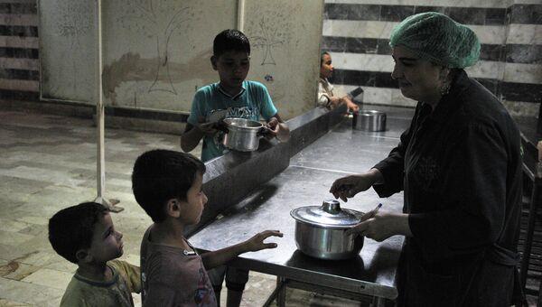 Раздача еды в лагере сирийских беженцев в спортивном комплексе имени Хафеза Асада, Латакия, Сирия. Архивное фото