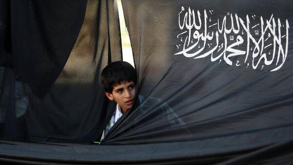 Палестинский мальчик на фоне флага партии Партии исламского освобождения. Архивное фото