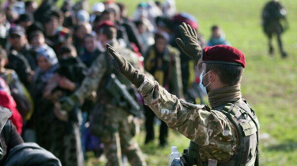 Словенский военный управляет движением беженцев, прибывших из Хорватии