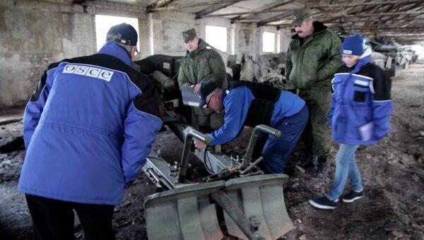 Представители ОБСЕ у военной техники, отведенной от линии соприкосновения ДНР, на специально подготовленной площадке в Донецкой области. Архивное фото
