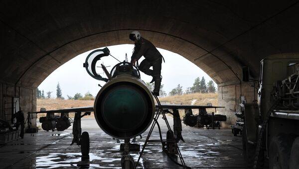 Сирийский летчик осматривает самолет МИГ-21 сирийских ВВС перед вылетом на авиабазе Хама