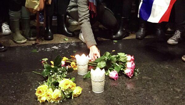 Люди возлагают цветы в Монреале в знак солидарности семьям погибших и пострадавших в терактах в Париже, 14 ноября 2015