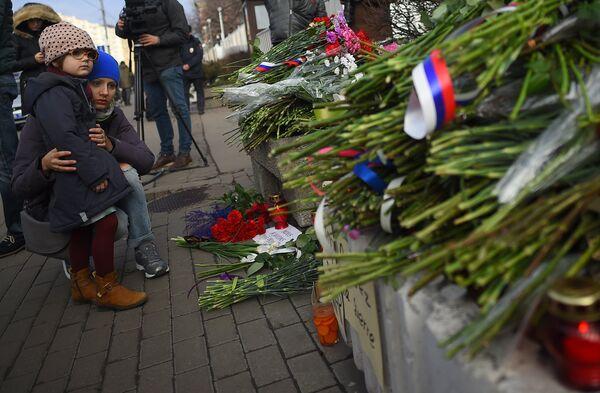 Люди оставляют цветы в память о погибших в теракте у посольства Франции в Москве