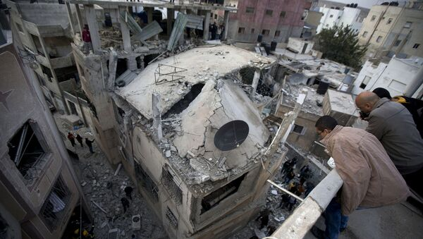 Палестинцы смотрят на дом, разрушенный израильской армией, на окраине города Рамалла. Архивное фото