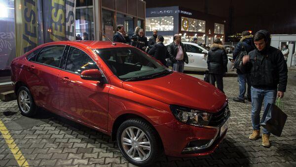 Молодые люди осматривают автомобиль Lada Vesta после начала продаж в Москве