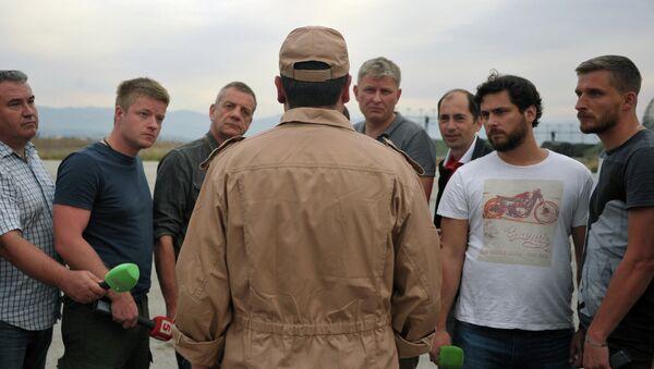 Спасенный летчик Су-24 Военно-космических сил России капитан Константин Мурахтин (в центре) отвечает на вопросы журналистов на авиабазе Хмеймим. Архивное фото