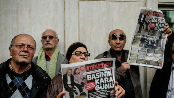 Люди держат выпуск газеты газеты Cumhuriyet возле здания редакции в Стамбуле. Архивное фото