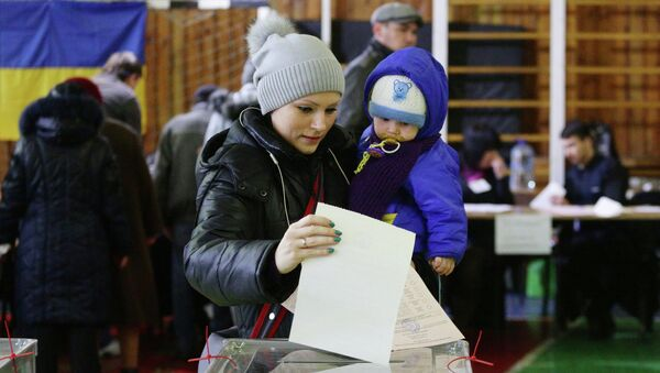 Женщина с ребенком на избирательном участке в Мариуполе