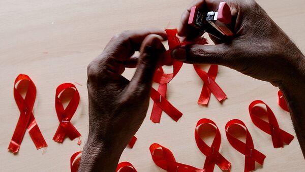 Мужчина делает красные ленточки, символ борьбы со СПИДом