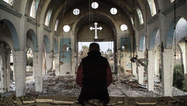 Житель одной из сирийских молится в храме, уничтоженном боевиками ИГ. Архивное фото
