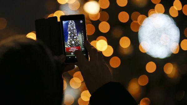 Человек фотографирует елку, в передней части готического собора Дуомо в Милане, Италия