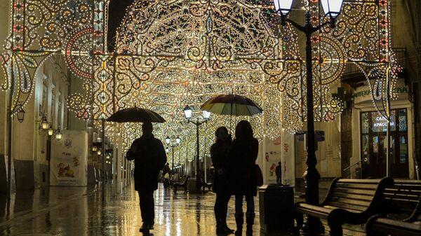 Прохожие во время дождя на Никольской улице в Москве