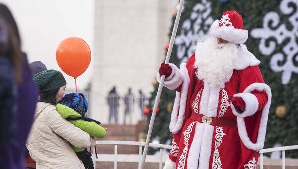 Аниматор в костюме Деда Мороза перед новогодней елкой на площади Ала-Тоо в Бишкеке