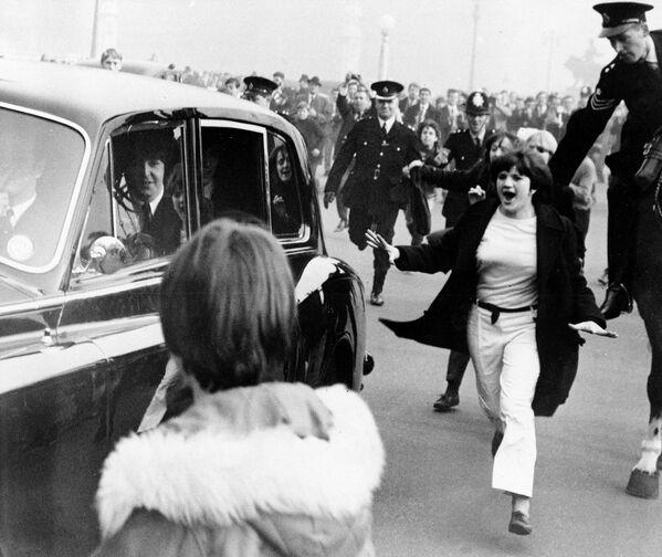 Автомобиль с участниками группы The Beatles в окружении фанатов. Лондон, Англия. 1965 год