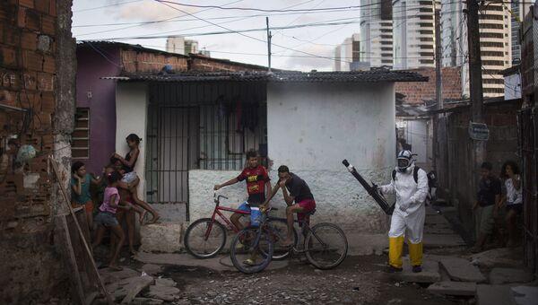 Медицинский работник распыляет инсектициды в жилом квартале в Ресифи, Бразилия