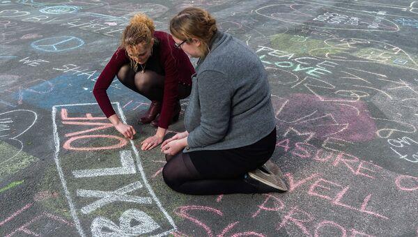 Люди рисуют мелом в память о жертвах терактов в Брюсселе возле Брюссельской фондовой биржи