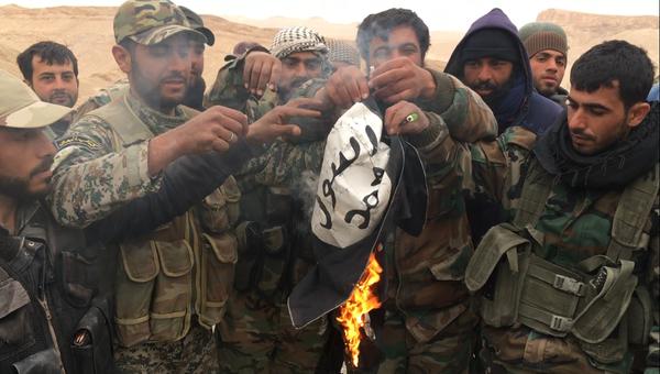 Сирийские солдаты сжигают флаг террористической группировки Исламское государство. Архивное фото