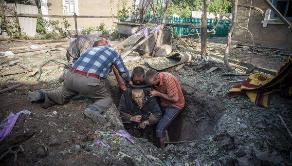 Местные жители достают из укрытия тело погибшего в результате обстрела поселка Александровка в Донецкой области. Архивное фото
