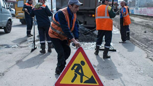 Рабочий устанавливает знак Дорожные работы на улице Кирова в Омске, где проходит ремонт дорожного покрытия