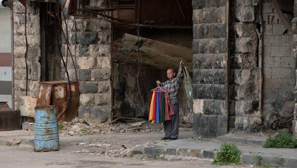 Мужчина торгует одеждой на одной из улиц Хомса. Сирия. Архивное фото
