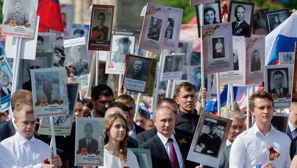Президент России Владимир Путин (в центре) с портретом своего отца-фронтовика Владимира Спиридоновича принимает участие в шествии патриотической акции Бессмертный полк на Красной площади. Архивное фото