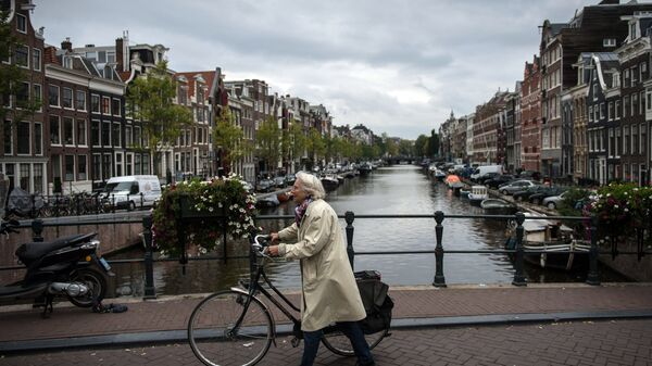 Пожилая женщина с велосипедом на мосту в центре Амстердама