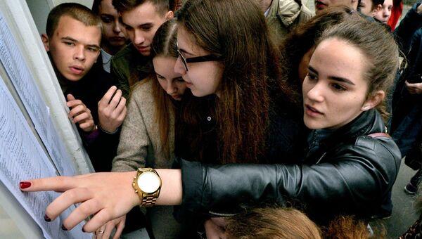 Ученики ищут свои фамилии в списках на сдачу ЕГЭ. Архивное фото