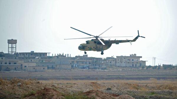 Вертолет сирийских ВВС совершает облет авиабазы Хама в пригороде города Хама сирийской провинции Хама