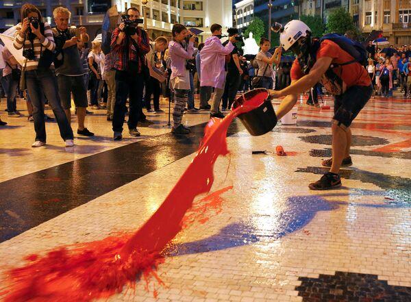 Активист разливает краску во время антиправительственной акции на центральной площади в Скопье, Македония. Июнь 2016