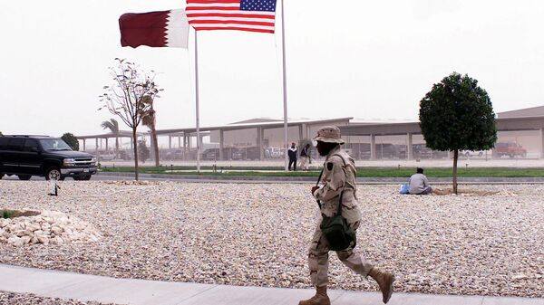 Американский военный на фоне флагов США и Катара