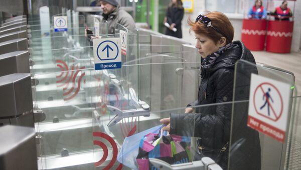 Пассажиры проходят турникеты в вестибюле станция метро. Архивное фото