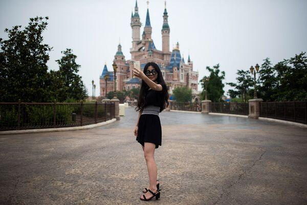 Посетительница первого на территории континентального Китая парка развлечений Диснейленд в Шанхае делает селфи