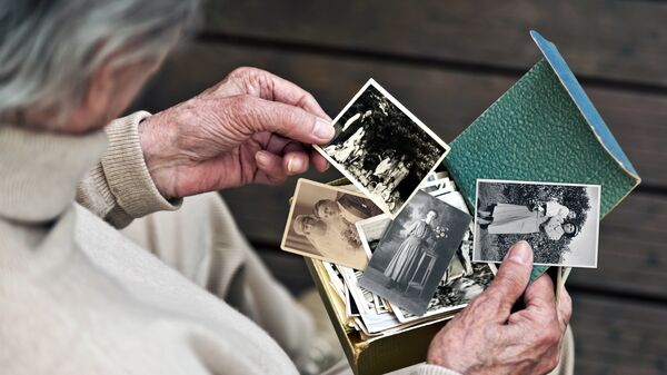 Пожилой человек рассматривает фотографии