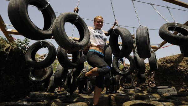 Участница Гонки героев на полигоне Ангарский в Симферопольском районе Крыма проходят полосу препятствий