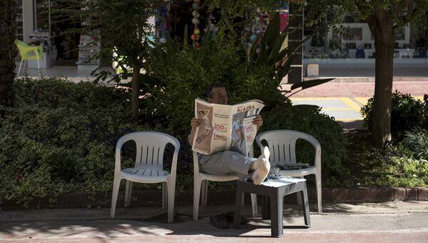 Мужчина читает газету на улице курорта Кемер в Турции. Архивное ыото