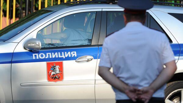 Полицейский автомобиль и сотрудник полиции в Москве. Архивное фото