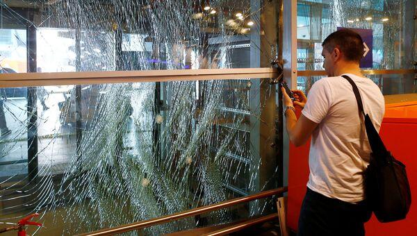 Человек фотографирует разбитые в результате теракта стекла в аэропорту Ататюрк. Стамбул, 29 июня 2016