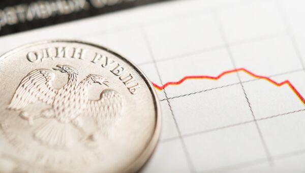 Монета в один рубль на фоне графика