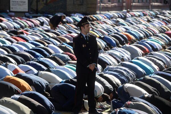 Сотрудник правоохранительных органов перед намазом в день праздника Ураза-байрам у Соборной мечети в Москве