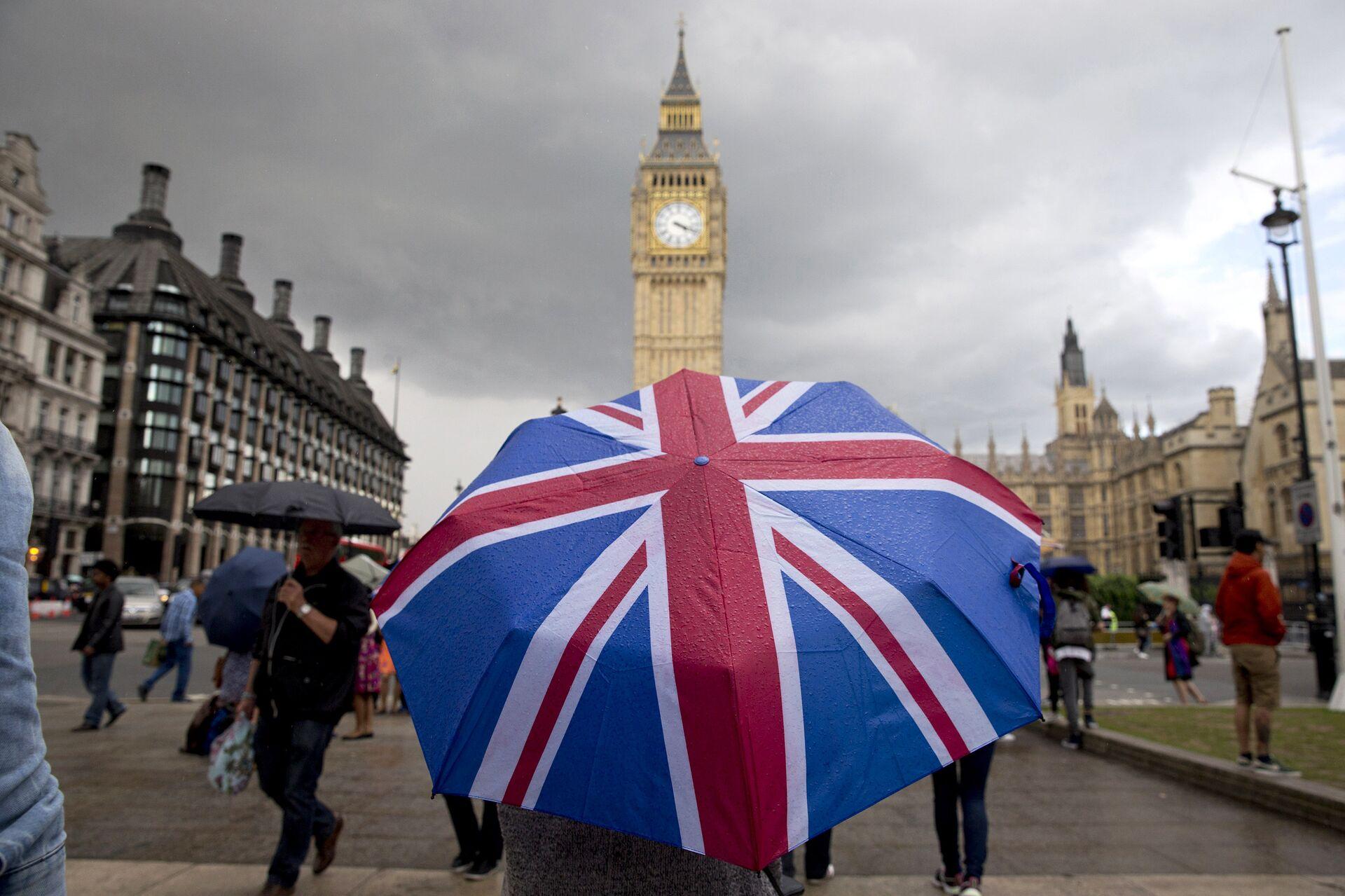 Человек с зонтом с флагом Великобритании у Биг Бена и здания парламента в Лондоне - РИА Новости, 1920, 14.12.2020