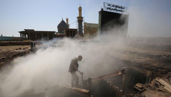 Полицейский на месте взрывов недалеко от шиитской святыни в городе Балад. 8 июля 2016