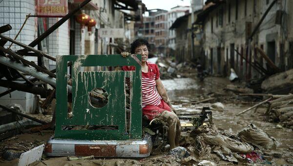 Женщина сидит на руинах после тайфуна Непартак в Китае