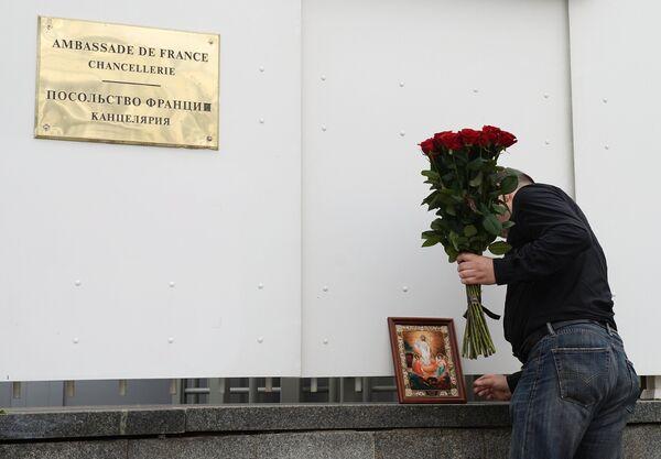 Мужчина возлагает цветы к посольству Франции в Москве в память о погибших в результате террористических акта в Ницце