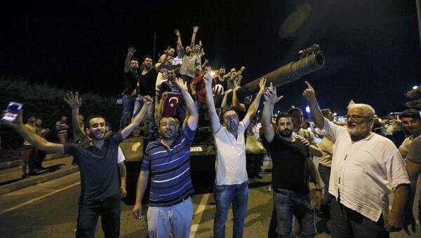 Люди вокруг танка турецкой армии рядом с аэропортом Ататюрка в Стамбуле. 16 июля 2016