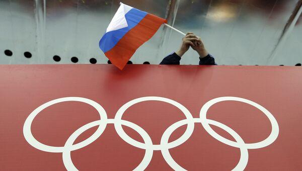 Болельщик держит российский флаг над логотипом олимпийских игр во время зимней Олимпиады-2014 в Сочи