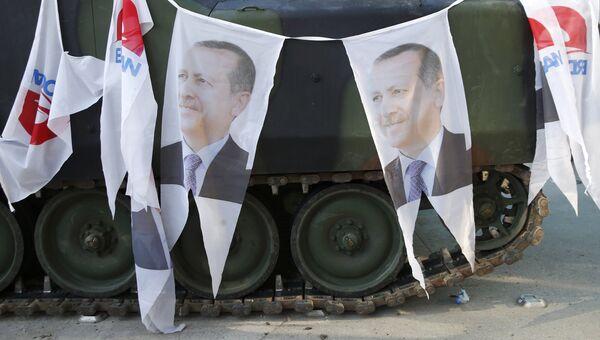 Портреты президента Турции Тайипа Эрдогана на бронетранспортере у здания парламента в Анкаре