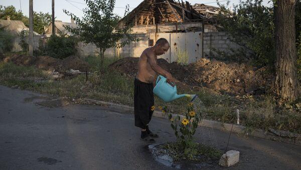 Мужчина поливает цветы на одной из улиц поселка Веселое Донецкой области