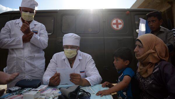 Российские врачи консультируют жителей населенного пункта Каукаб в Сирии во время раздачи российской гуманитарной помощи
